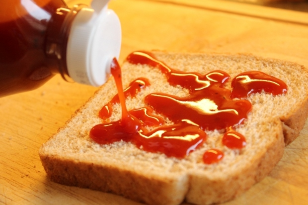 Pouring barbecue sauce on one side of bread slice.
