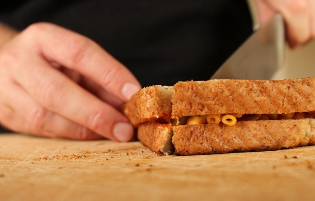 Cutting Grilled Mac and Cheese Sandwich in half.